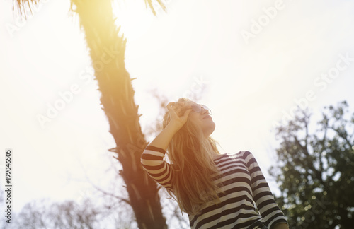 A young woman traveller with sunglasses staying near a palm on sunny warm day. Traveler, vacation, successful woman