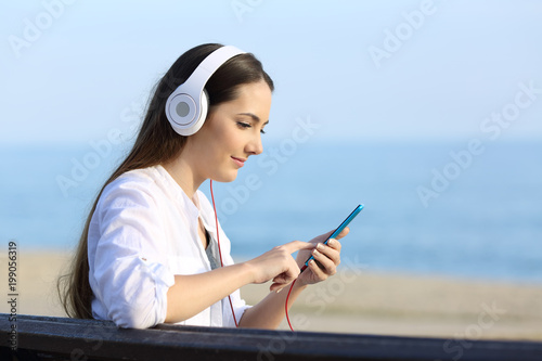 Girl listening to music and choosing song on line - 199056319