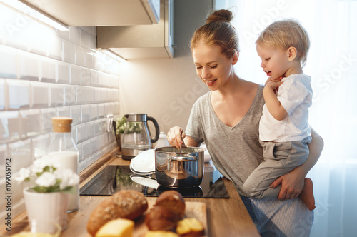 preparation of family breakfast. mother and baby son cook porridge in morning