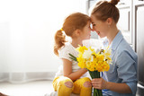 happy mother's day! child daughter   gives mother a bouquet of flowers to narcissus and gift - 199059391