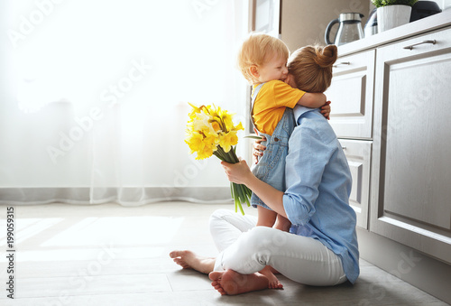 happy mother's day! baby son gives flowersfor  mother on holiday