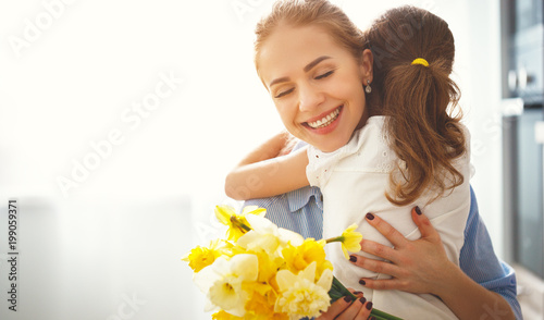 happy mother's day! child daughter   gives mother a bouquet of flowers to narcissus and gift