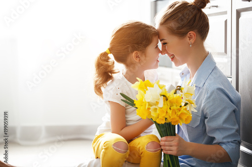 Fototapeta happy mother's day! child daughter gives mother a bouquet of flowers to narcissus and gift