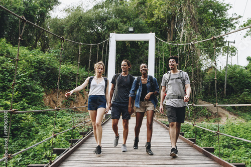 Fotobehang Hoogte schaal Group of friends walking on the bridge in a tropical countryside adventure and journey concept