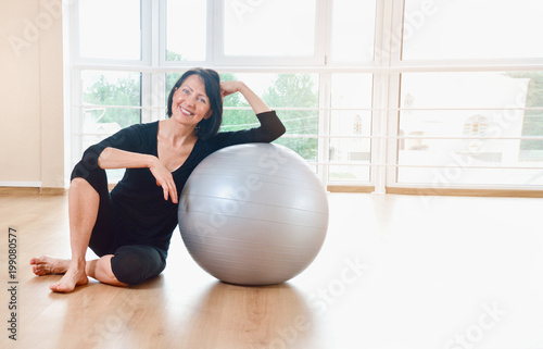 Happy senior woman resting after exercise with gray exercise ball