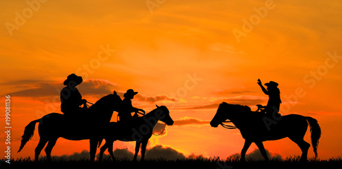 Poster Oranje eclat silhouette Cowboy riding a horse on sunrise
