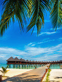 Beautiful exotic beach and wooden bridge to amazing exotic bungalows on turquoise water - 199086990