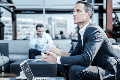 Thoughtful look. Pleasant nice thoughtful businessman holding his notebook and thinking about his work while sitting in front of the laptop