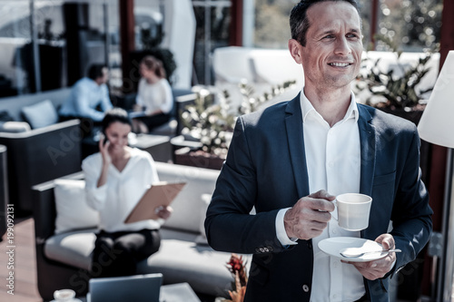 Wonderful mood. Cheerful happy handsome businessman drinking coffee and smiling while enjoying his drink - 199092131