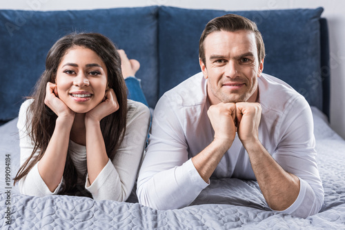 happy multiethnic couple lying on bed and smiling at camera