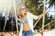 Beautiful young curly funny girl on a swing on a tropical beach, freedom, vacation, travel, joy and happiness concept