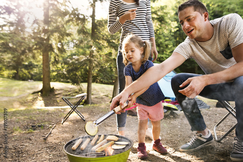 Family camping in forest, cooking meat on barbecue grill.