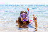 Woman on beach vacation holidays with snorkel lying in sea with snorkeling mask smiling happy enjoying the sun on sunny summer day. Beautiful young woman with snorkeling equipment at the sea coast - 199107767
