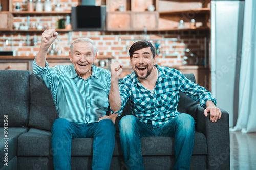 Happy positive men watching football
