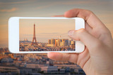 Closeup of a hand with smartphone taking a picture of  Paris with the Eiffel tower at sunset,  France - 199113982
