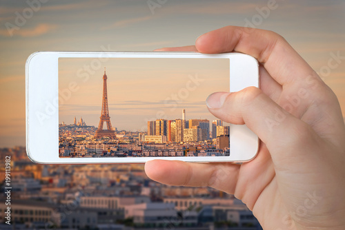 Closeup of a hand with smartphone taking a picture of Paris with the Eiffel tower at sunset, France