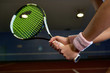 Close up of unrecognizable woman holding racket while playing tennis in indoor court and swinging to hit ball, copy space