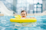 Little cute toddler swimming in a swim ring