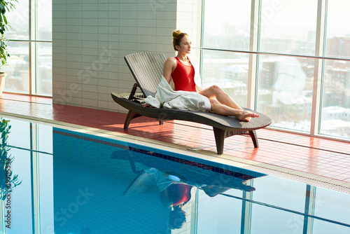 Full length portrait of beautiful young woman relaxing in wicker lounge chair by swimming pool in hotel, copy space
