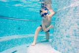 Boy playing in a swimming pool with goggles on