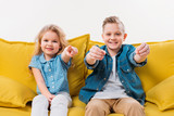 little boy driving and sister pointing while sitting on yellow sofa - 199118363
