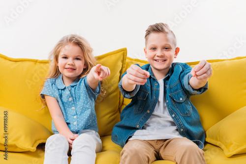 mały chłopiec jazdy i siostra wskazując siedząc na żółtej kanapie