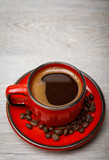 A red cup of tasty coffee on wooden background