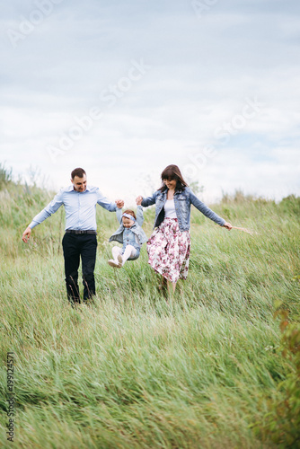Daughter holds hands mom and dad. Hands in the hands. A young family is walking with a little daughter in the outdoors along the green grass. Happy family together.