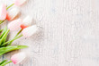 Mother's Day concept, greeting card background. Flowers tulips on a light concrete table, copy space top view