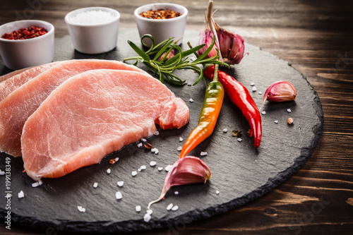 Raw pork chops on cutting board and vegetables - 199138349