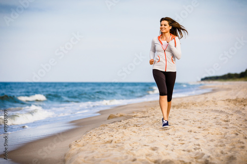 Young woman running, jumping on beach
