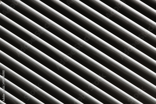 An abstract snapshot of a close-up illuminated grille that is angled with a dark background for patterns and backgrounds. - 199140981