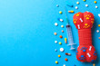 Toy rubber bone for dogs and many colored tabbies with a syringe on a blue background. The concept of a vetenary clinic for the treatment of pets