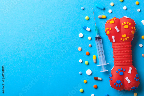 Foto Murales Toy rubber bone for dogs and many colored tabbies with a syringe on a blue background. The concept of a vetenary clinic for the treatment of pets