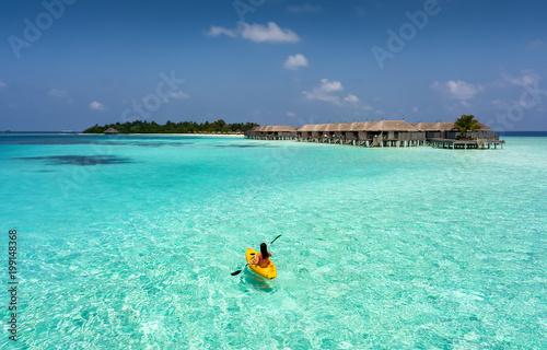 Frau im Kajak paddelt über die türkise Gewässer der Malediven