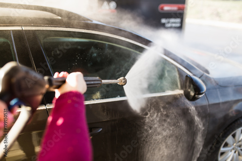 Myjnia samochodowa. Czyszczenie samochodu przy użyciu wody pod wysokim ciśnieniem. Selektywna ostrość.