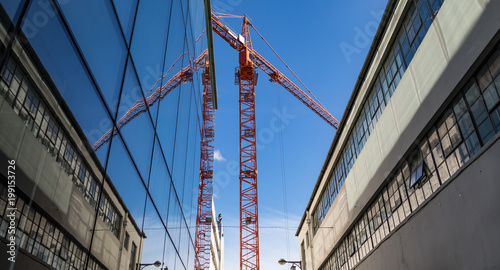 Red construction crane reflected in glass windows of building a city