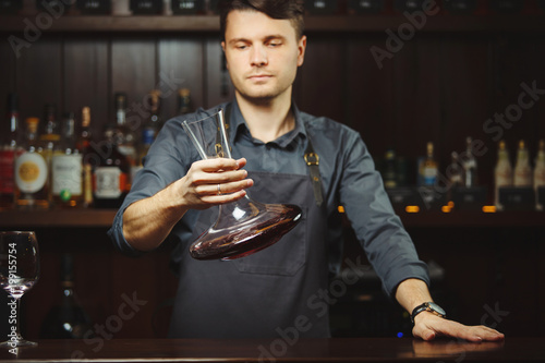 Bartender decanting wine without disturbing the sediment © Ilshat