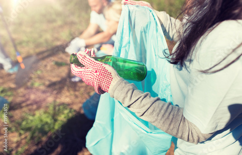 volunteering, people and ecology concept - volunteer woman with garbage bag and glass bottle cleaning area in park - 199158511