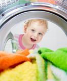 happy kid looking inside wash machine with clothes