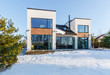 A modern house with large panoramic windows in the background of a snow-covered landscape