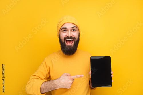 Stylowy młody człowiek promujący tabletkę