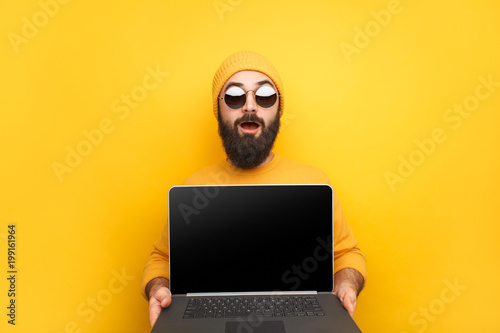 Trendy man advertising laptop