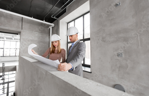 architecture, construction business and people concept - architects with blueprint and helmets at office