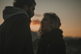 Close up portrait of cool couple looking to each other at sunset with an orange sky in the background. - 199163940