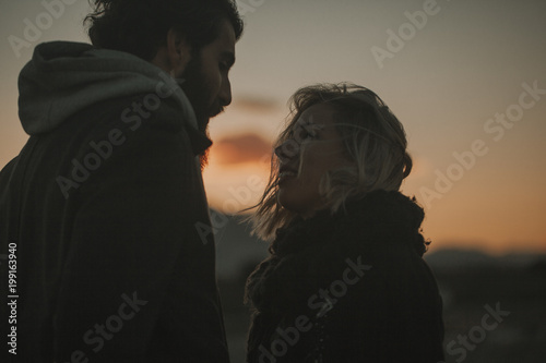 Close up portrait of cool couple looking to each other at sunset with an orange sky in the background Poster
