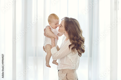 Foto Murales Mother with a baby in her arms plays against the window. Mothers Day.