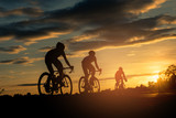 The men ride bikes at sunset with orange-blue sky background. Abstract Silhouette background concept.