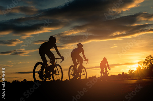 The men ride  bikes at sunset with orange-blue sky background. Abstract Silhouette background concept. - 199164985