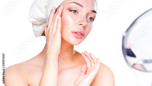 Portrait of beautiful girl touching her face with a towel on  head © lenets_tan